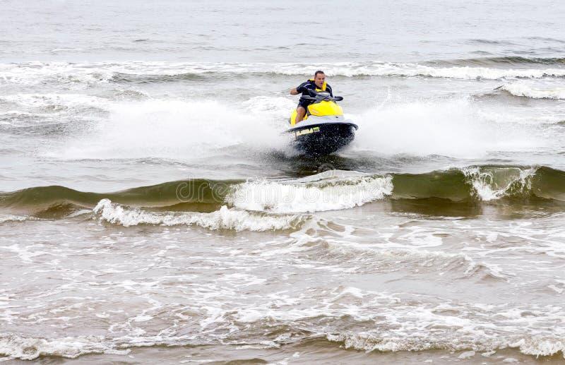 Le jeune homme exécutant des tours sur le ski de jet sur la mer ondule image stock