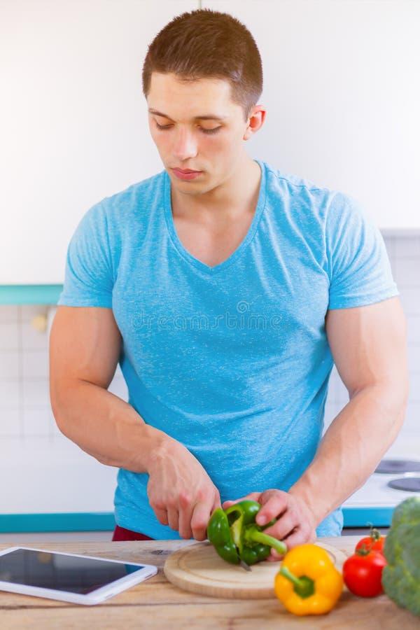 Le jeune homme faisant cuire les légumes sains de repas marquent sur tablette le portra d'Internet photos libres de droits