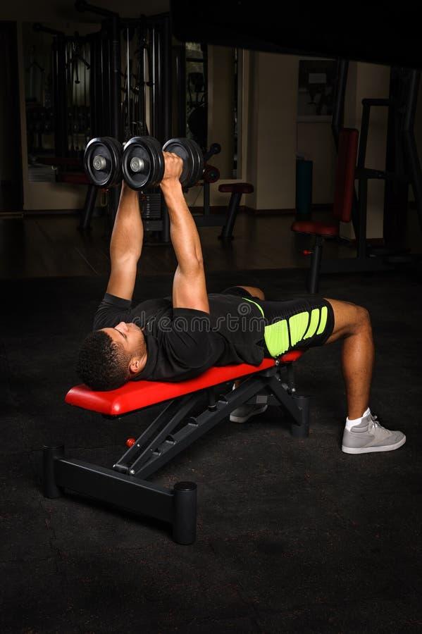 Le jeune homme faisant le banc de bras pilote la séance d'entraînement dans le gymnase photographie stock