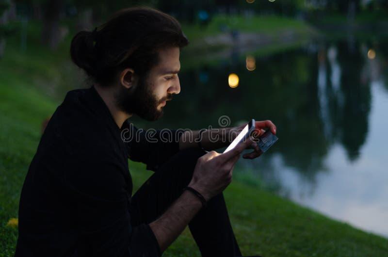 Le jeune homme fait des emplettes au téléphone mobile images libres de droits