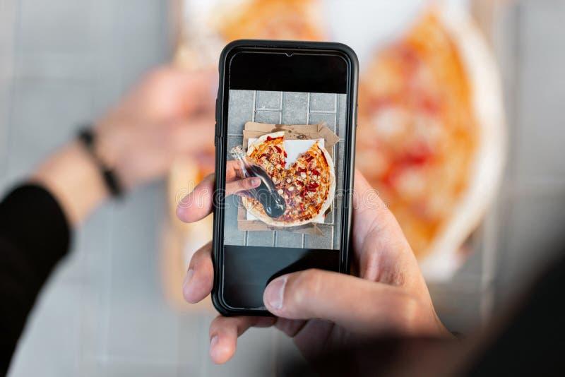 Le jeune homme fait une photo de la pizza délicieuse sur un smartphone Plan rapproché des mains et de l'image masculines de pizza image libre de droits