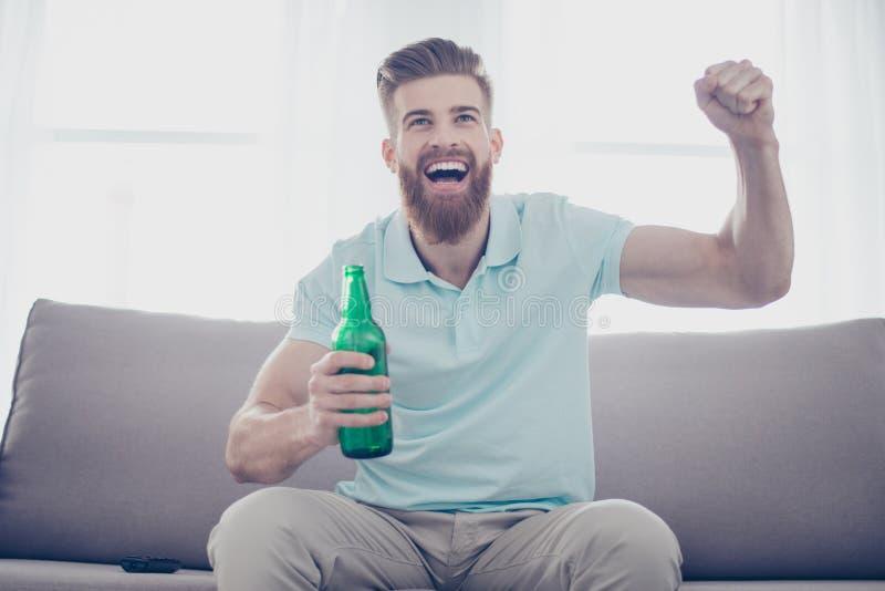 Le jeune homme gai est heureux en raison du but de son favori photo stock