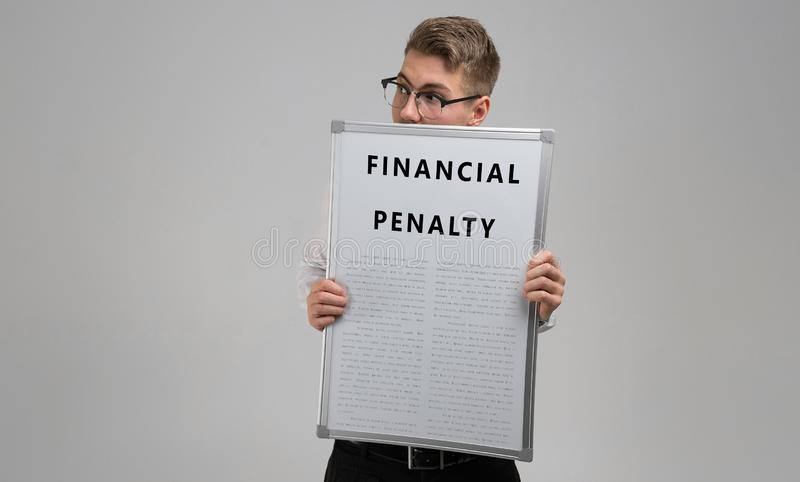 Le jeune homme garde devant lui qu'une affiche avec la pénalité financière est sur un fond clair photographie stock libre de droits