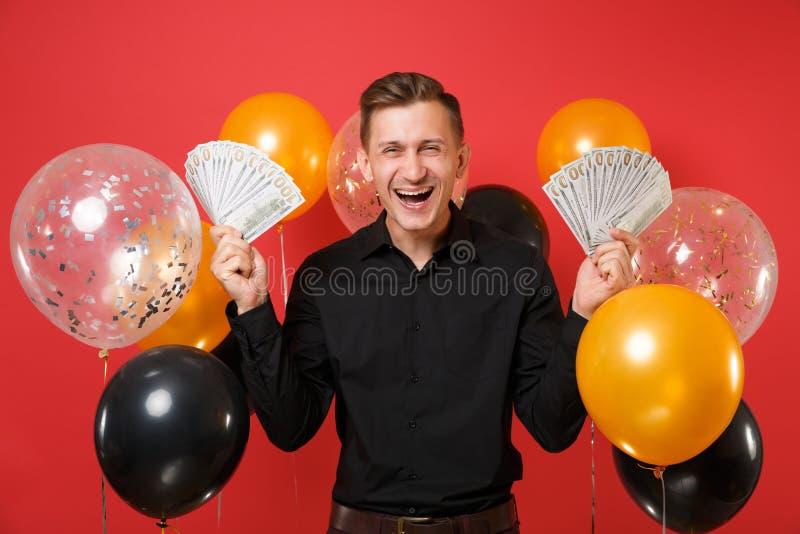 Le jeune homme heureux dans un bon nombre classiques noirs de paquet de participation de chemise de dollars encaissent l'argent s images libres de droits