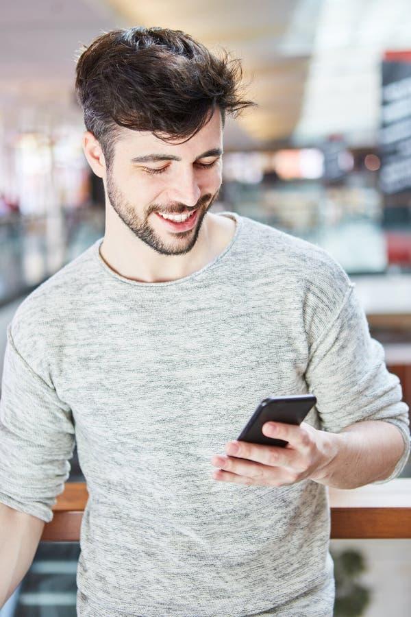 Le jeune homme heureux lit un message textuel photographie stock libre de droits