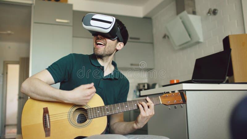 Le jeune homme heureux s'asseyant à la cuisine apprenant à jouer la guitare utilisant le casque de VR 360 et le sent guitariste a image stock