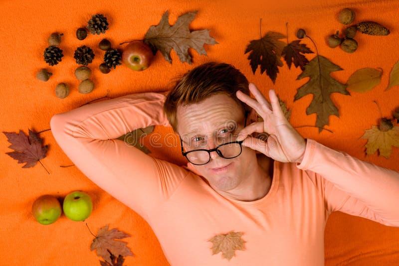 Le jeune homme heureux se préparent à la vente d'automne Étonnez l'homme de tête de lecture jouant avec des feuilles et regardant image libre de droits