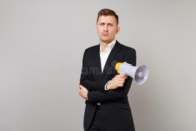 Le jeune homme indifférent d'affaires dans le costume noir classique, chemise tenant des mains avec le mégaphone s'est plié d'iso images libres de droits