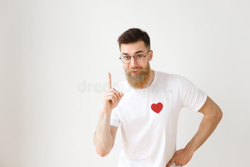 Le jeune homme intelligent avec la longue barbe épaisse soulève le doigt antérieur comme obtient idée brillante, porte autour des image libre de droits