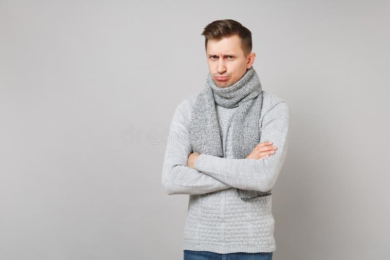 Le jeune homme irrité dans le chandail gris, lèvres boudantes d'écharpe, tenant des mains a croisé d'isolement sur le fond gris S photo stock