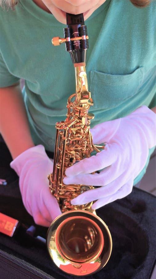 Le jeune homme joue le mini saxophone tout en portant les gants blancs photo stock