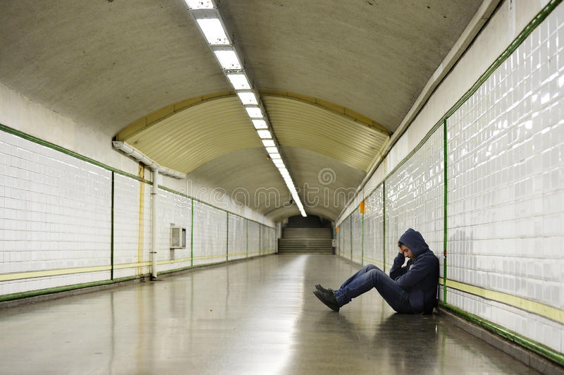Le jeune homme malade a perdu la dépression de souffrance se reposant sur le tunnel moulu de souterrain de rue photo stock