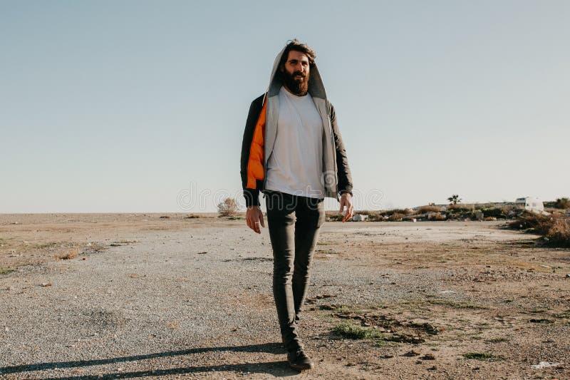 Le jeune homme marchant dehors au coucher du soleil avec le frappeur urbain vêtx le style image stock
