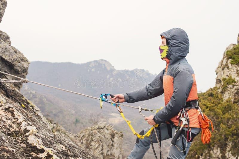 Le jeune homme monte la roche sur une corde avec les ceintures de sécurité, assurance et corde, dans le plein équipement d'alpini image stock