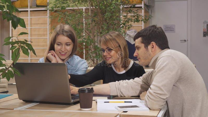 Le jeune homme montre à ses collègues quelque chose sur l'ordinateur portable au hub fonctionnant images stock