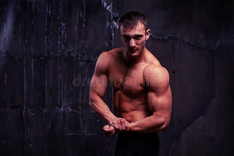 Le jeune homme musculaire de torse nu a pompé son bras image stock