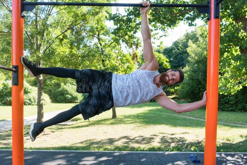 Le jeune homme musculaire faisant le poids du corps s'exerce en parc moderne de forme physique photos libres de droits