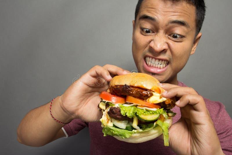 Le jeune homme ont un grand désir de manger un hamburger images libres de droits
