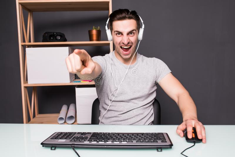Le jeune homme ou le pirate informatique dans le casque et des lunettes avec l'ordinateur de PC jouant le jeu et coulant la vidéo photographie stock