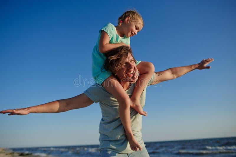 Le jeune homme passe gaiement le temps avec la petite fille par la mer image stock