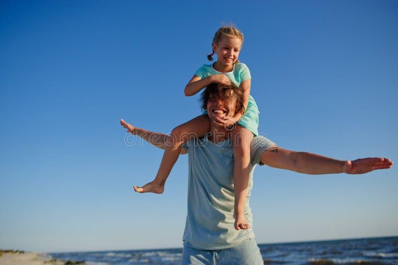 Le jeune homme passe gaiement le temps avec la petite fille par la mer images stock