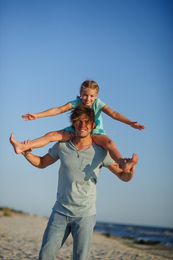 Le jeune homme passe gaiement le temps avec la petite fille sur la plage sablonneuse photos libres de droits