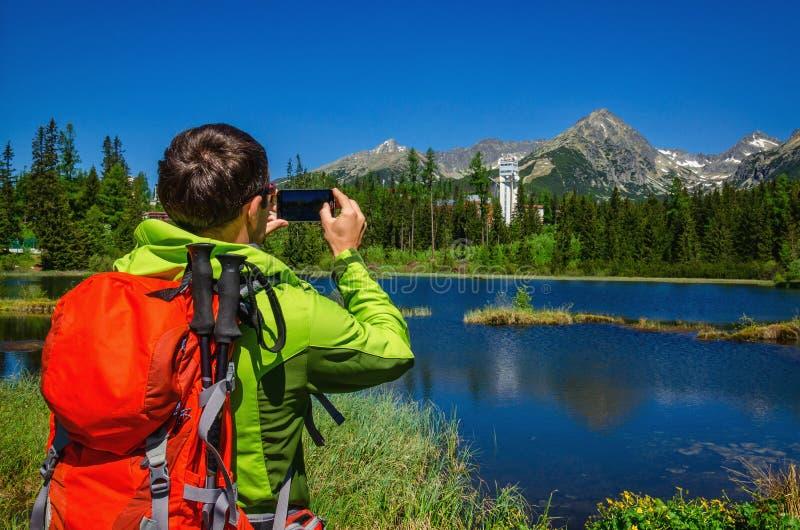 Le jeune homme prend la photo des montagnes et du lac photographie stock