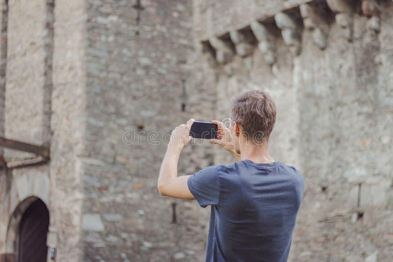 Le jeune homme prend une photo d'un ch?teau images stock