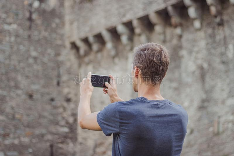 Le jeune homme prend une photo d'un ch?teau image libre de droits