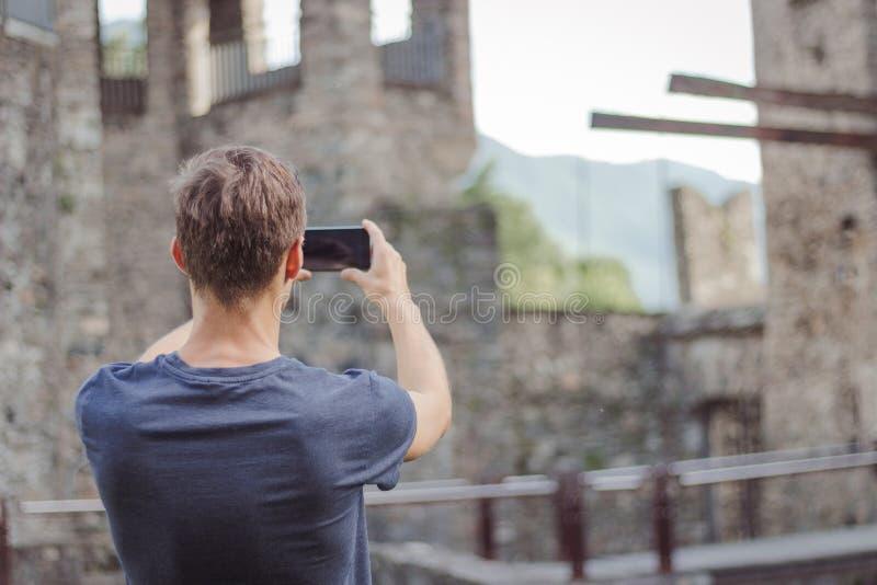 Le jeune homme prend une photo d'un ch?teau image stock
