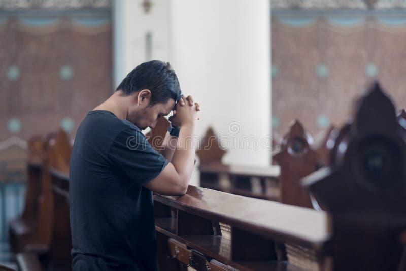 Le jeune homme prie avec les mains étreintes dans l'église photo stock