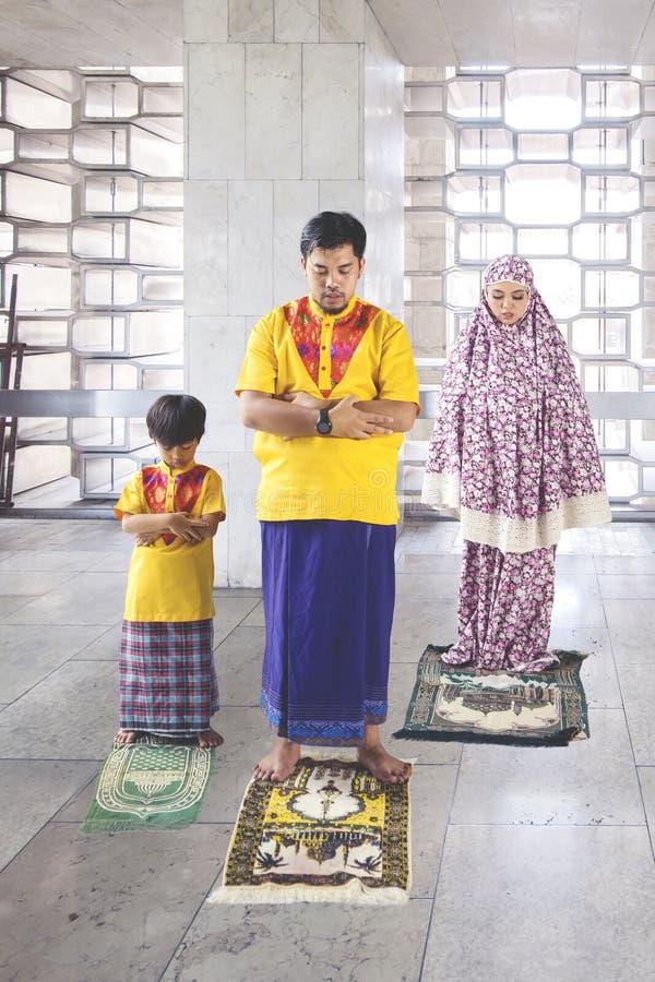 Le jeune homme prie avec son fils et épouse dans la mosquée photo libre de droits