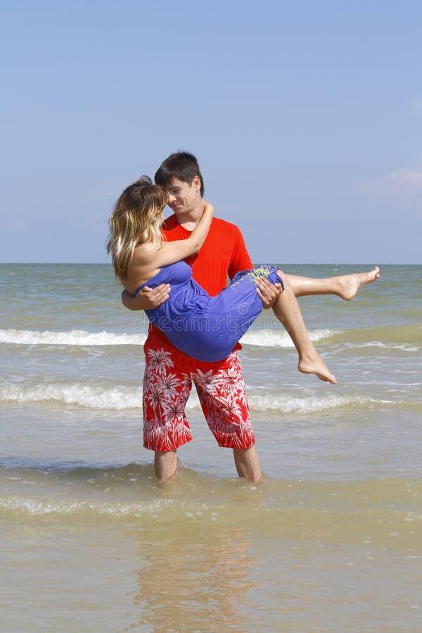Le jeune homme a pris la fille dans des ses bras photographie stock