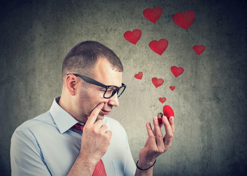 Le jeune homme réfléchi regardant une bague de fiançailles et a des doutes photos stock