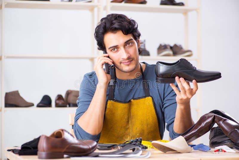 Le jeune homme réparant des chaussures dans l'atelier photographie stock