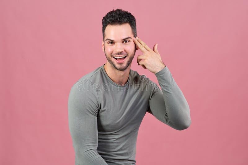 Le jeune homme réussi de sports sourit heureusement et met sa main pliée comme une arme à feu à sa tête photo libre de droits
