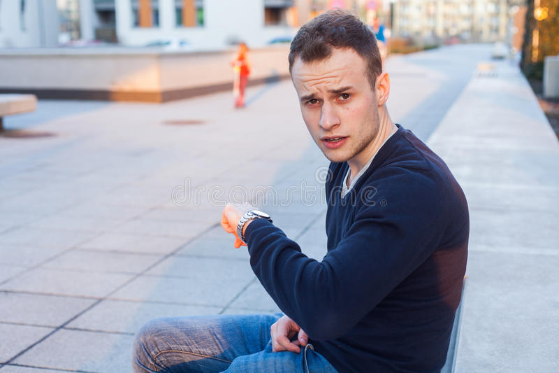 Le jeune homme regarde sa montre vérifiant le temps. photo libre de droits