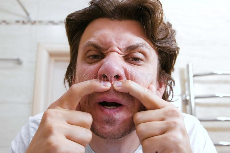 Le jeune homme regardent le miroir et serrent un bouton sous son nez Visage de plan rapproché image stock