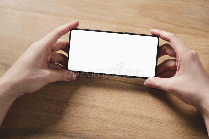 Le jeune homme remet tenir le smartphone avec l'écran blanc vide images libres de droits