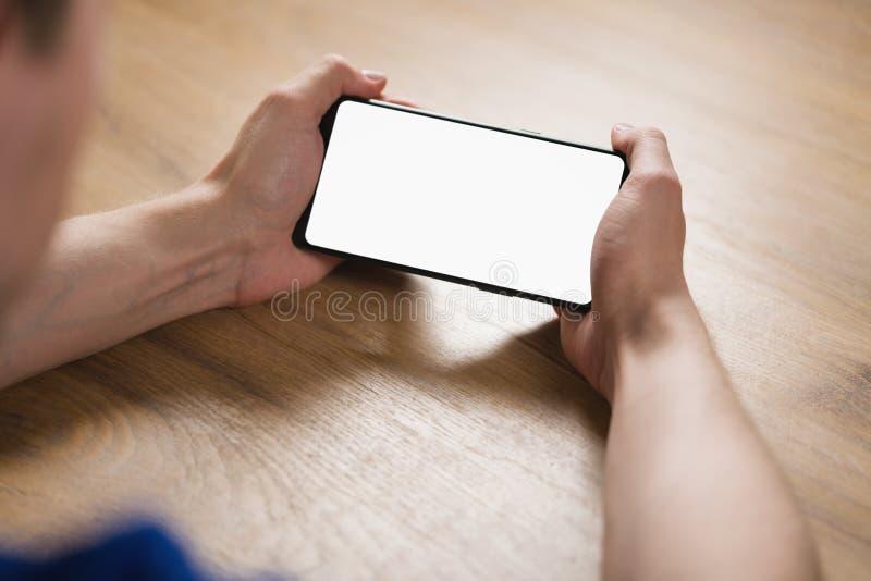 Le jeune homme remet tenir le smartphone avec l'écran blanc vide en en largeur images stock