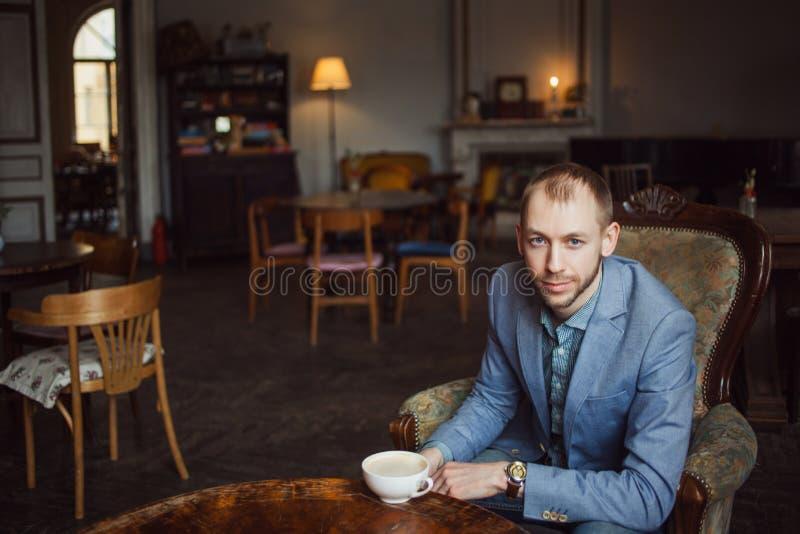 Le jeune homme repose et apprécie le café pendant le matin Portrait dans l'intérieur photo stock