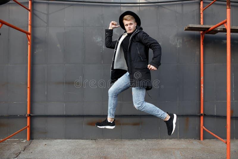 Le jeune homme roux élégant dans l'équipement à la mode ont l'amusement et sauter contre le mur urbain dehors image libre de droits