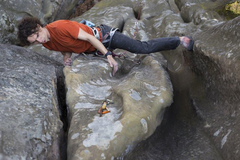 Le jeune homme s'élève sur une falaise avec une corde photos stock