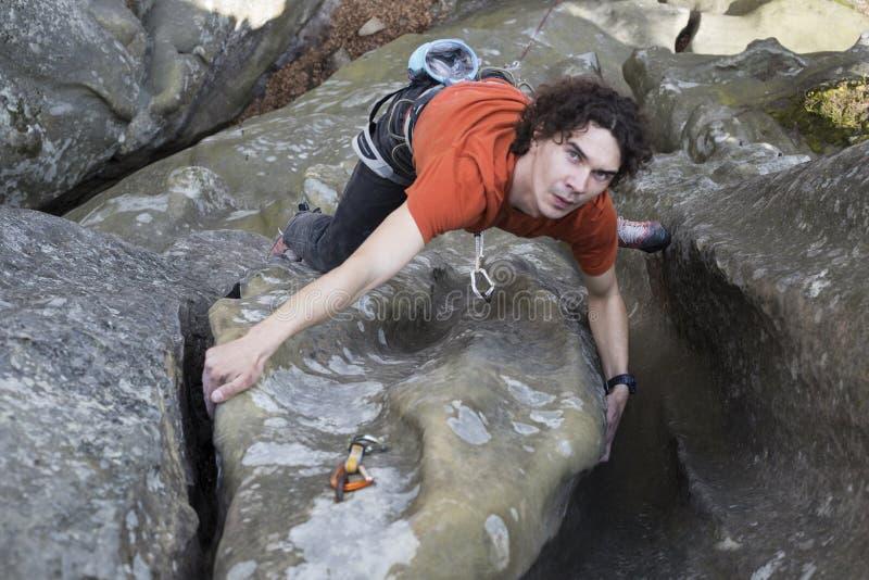 Le jeune homme s'élève sur une falaise avec une corde images stock