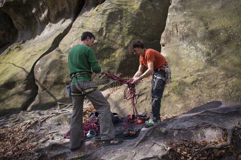 Le jeune homme s'élève sur une falaise avec une corde images libres de droits