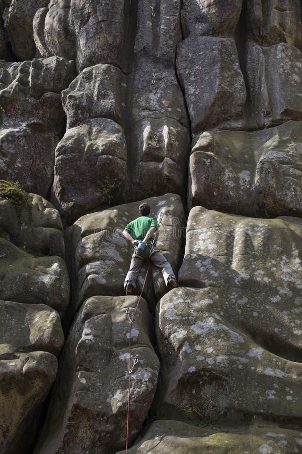 Le jeune homme s'élève sur une falaise avec une corde photo stock