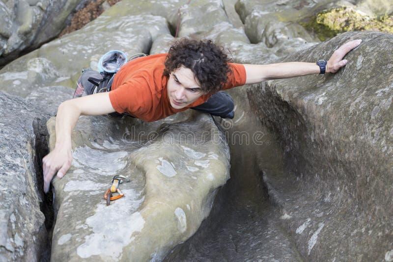Le jeune homme s'élève sur une falaise avec une corde photo libre de droits