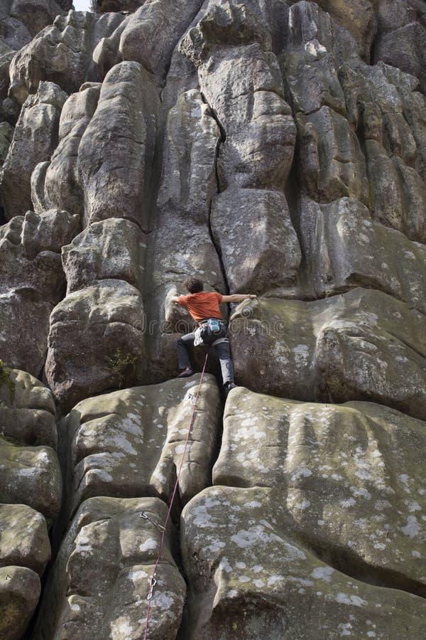 Le jeune homme s'élève sur une falaise avec une corde image stock