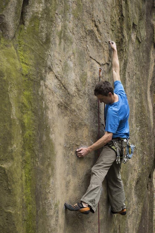 Le jeune homme s'élève sur une falaise avec une corde photographie stock libre de droits
