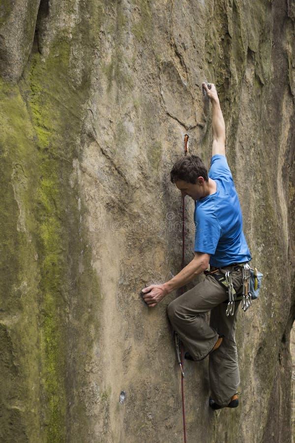 Le jeune homme s'élève sur une falaise avec une corde image libre de droits
